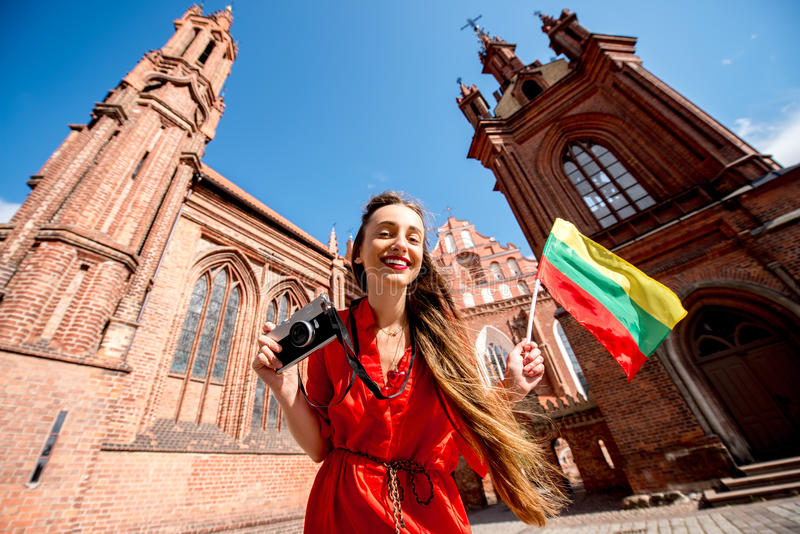 Woman traveling in Vilnius. Young female tourist with photo camera and lithuanian flag standing in front of the famous gothic church in the old town of Vilnius stock photos