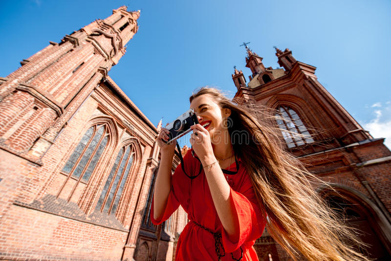 Woman traveling in Vilnius. Young female tourist with photo camera standing in front of the famous gothic church in the old town of Vilnius. Woman having great stock photos