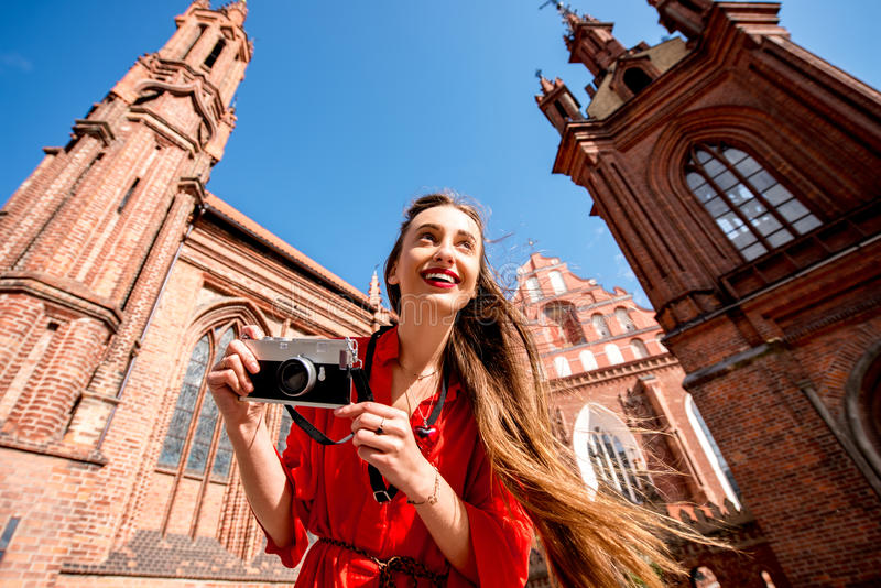 Woman traveling in Vilnius. Young female tourist with photo camera standing in front of the famous gothic church in the old town of Vilnius. Woman having great stock image
