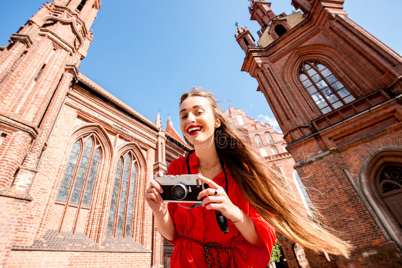 Woman traveling in Vilnius. Young female tourist with photo camera standing in front of the famous gothic church in the old town of Vilnius. Woman having great royalty free stock images