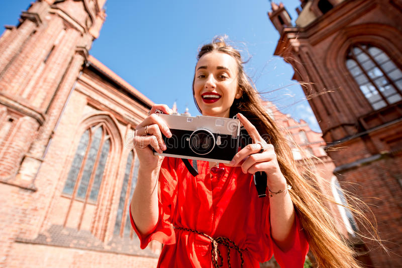 Woman traveling in Vilnius. Young female tourist with photo camera standing in front of the famous gothic church in the old town of Vilnius. Woman having great royalty free stock photos