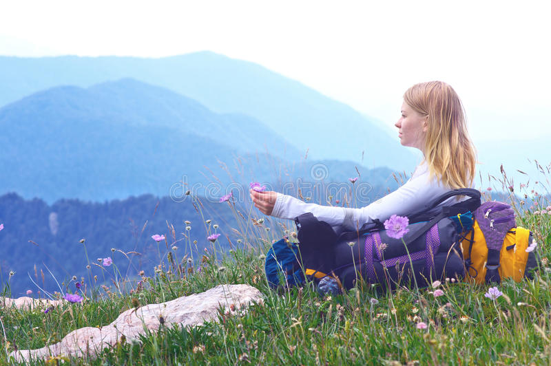 Woman Traveller with backpack sitting on grass with flowers relaxing. With Mountains on Background stock photo