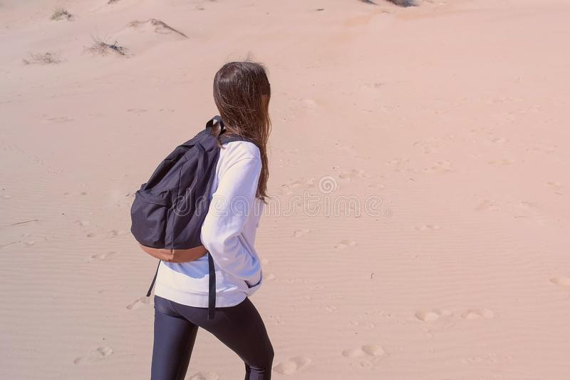 Woman tourist is walking among sand dune on sea beach outdoor activity vacation. Woman traveller with backpack in sportswear is walking on sand dunes on stock photo
