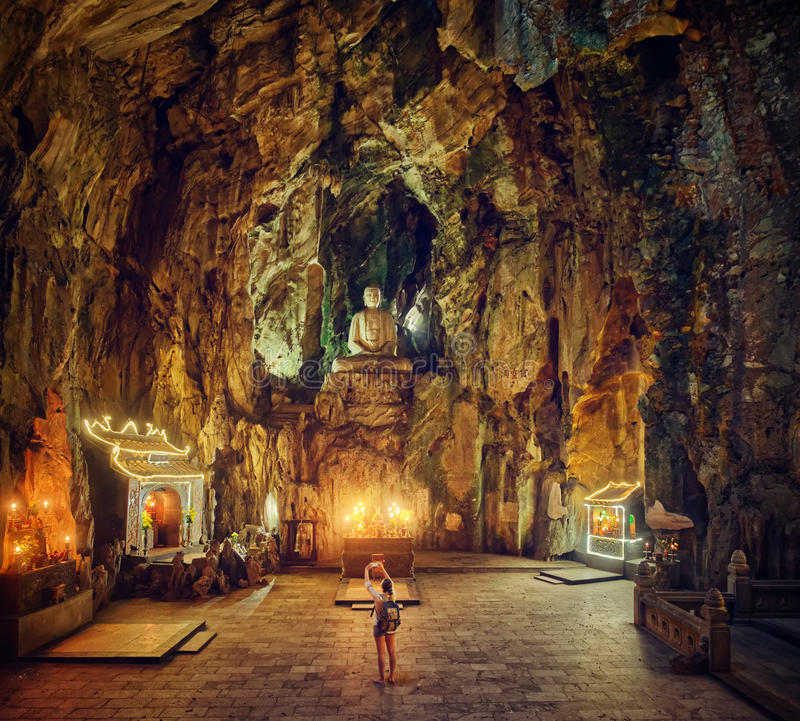 Woman traveller the photographing on the smartphone Buddhist pagoda in cave stock images