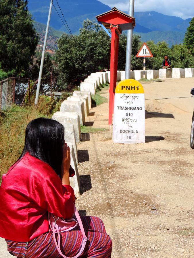 Woman traveller and signboard mentioning distance to destination royalty free stock photography
