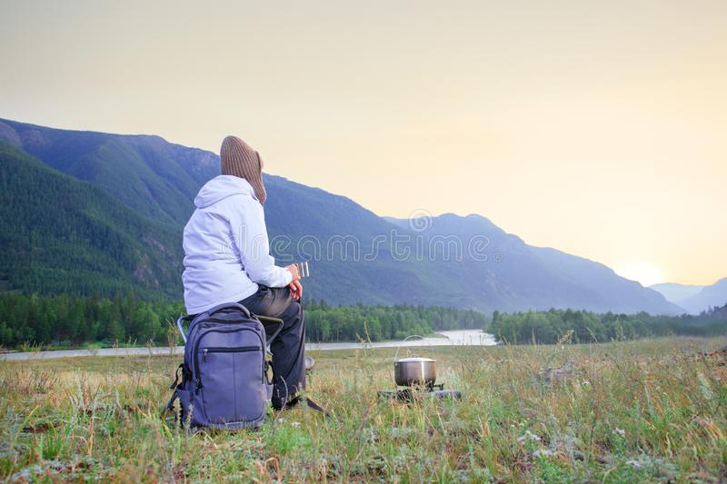Woman traveller sitting and enjoying hot tea in a mug. Woman hiking in mountains royalty free stock photo