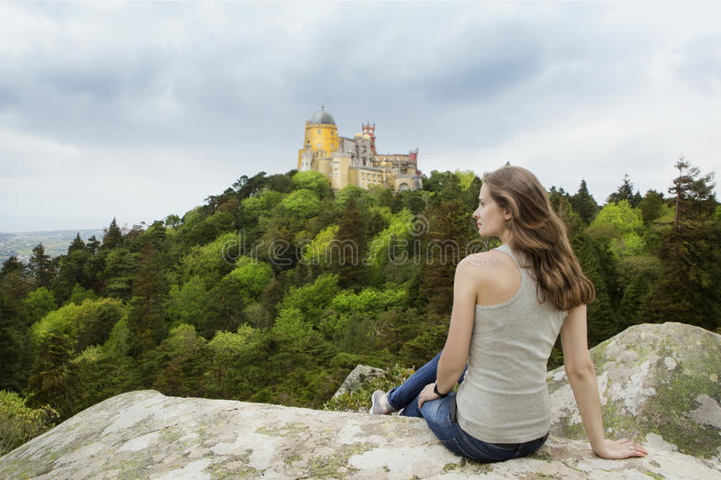 Woman is travelling to Europe. Beautiful girl sitting on the edge of the mountain and thoughtfully dreamily looking at Pena Palace in Portugal royalty free stock photography