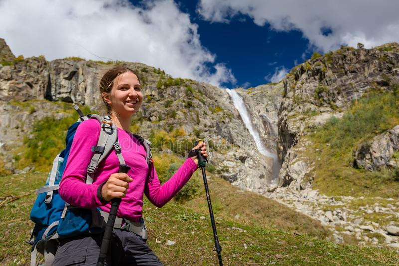 Woman trekking in Caucasus mountains against high waterfal in Us royalty free stock photos