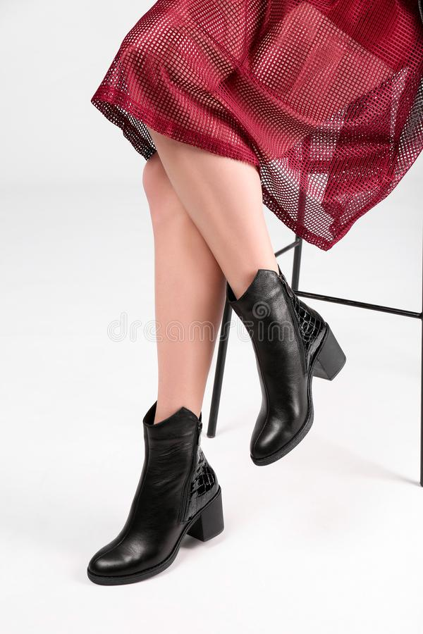 Woman in trendy shoes sitting on bar stool. Light background stock image