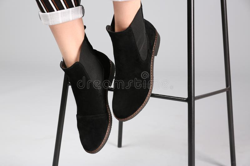 Woman in trendy shoes sitting on bar stool. Light background royalty free stock photos