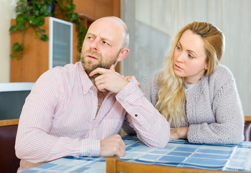 Woman tries reconcile with man. Loving women tries reconcile with men after quarrel at home. Focus on guy stock images
