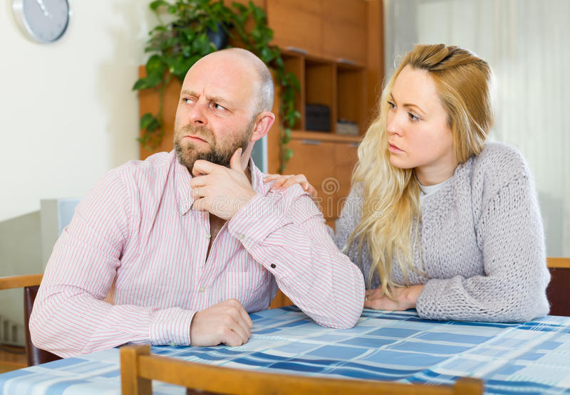 Woman tries reconcile with man. Woman tries reconcile with men after quarrel at home. Focus on guy royalty free stock photos