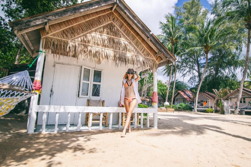Woman tropical bungalow vacation on green background. Summer vacation. Beautiful sand beach. stock images