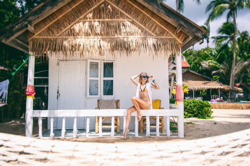Woman tropical bungalow vacation on green background. Summer vacation. Beautiful sand beach. stock photos