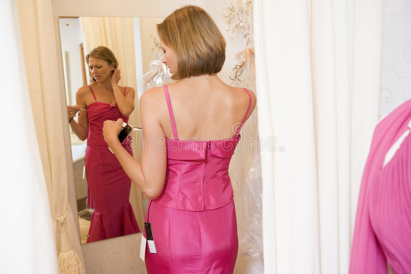 Woman trying on dresses and frowning.  stock photography