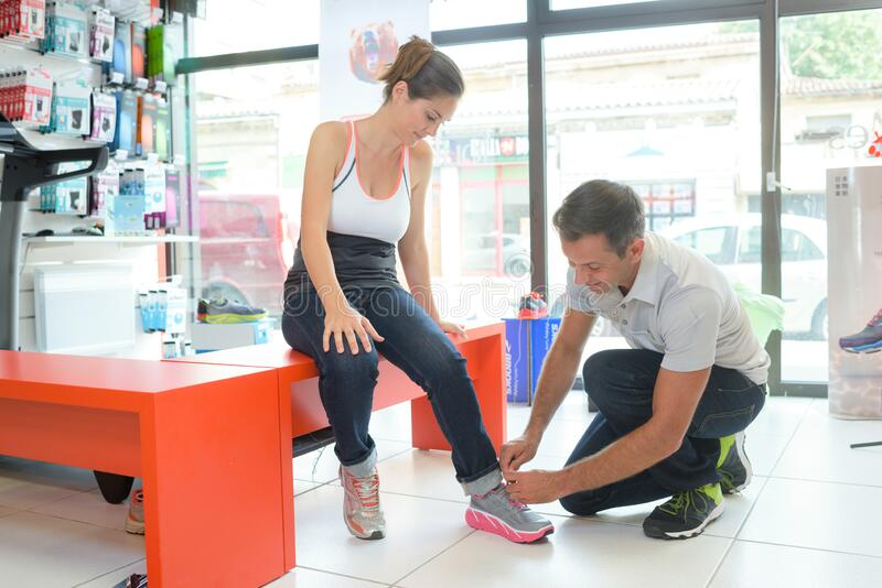 Woman trying ergonomic designed shoes. Boutique stock photo