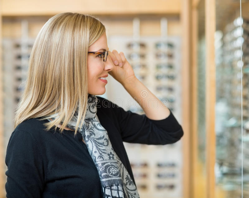 Woman Trying On Glasses In Optician Store royalty free stock photo