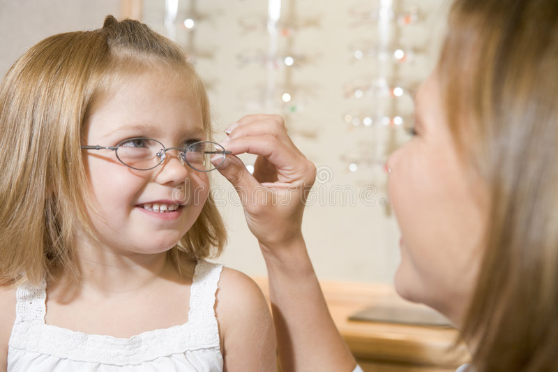 Woman trying glasses on young girl at optometrists stock images