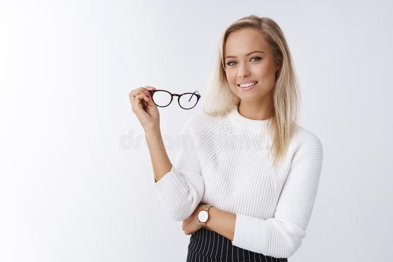 Woman trying new glasses in store picking right frame fits style posing over white background confident and satisfied royalty free stock photos