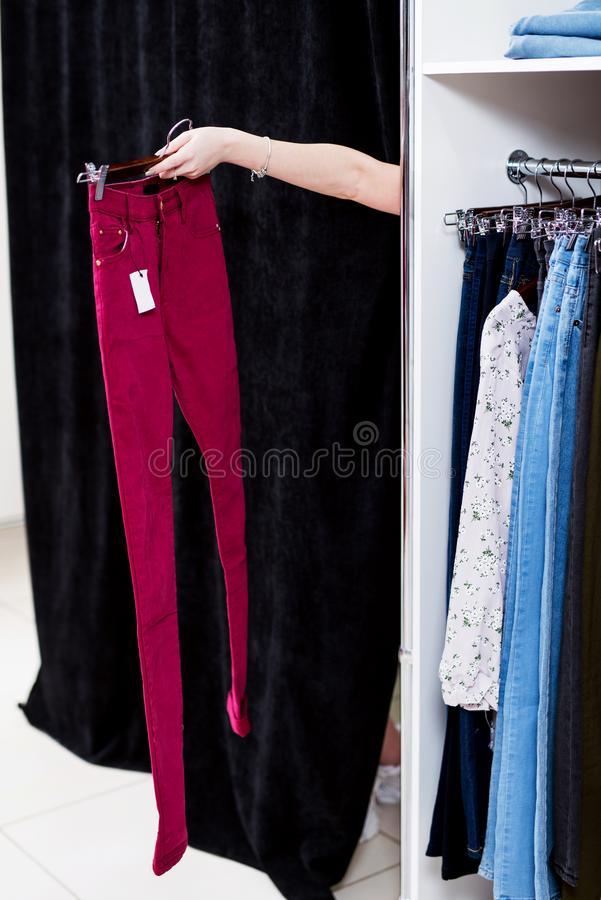 Woman trying on pants in a clothing store reaching out hand from a fitting room holding trousers.  royalty free stock photography