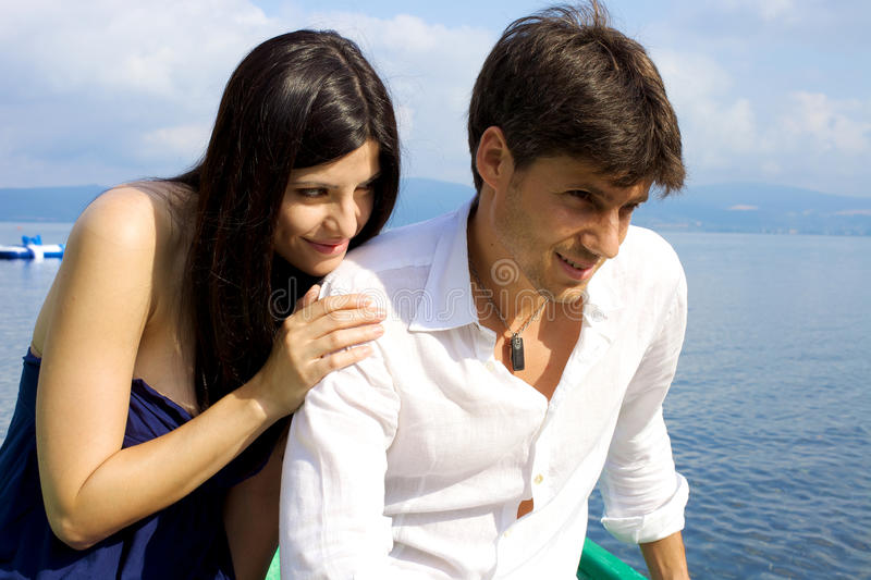 Woman trying to be forgiven from boyfriend. Couple in vacation in Italy after fight get reunited on lake royalty free stock photo