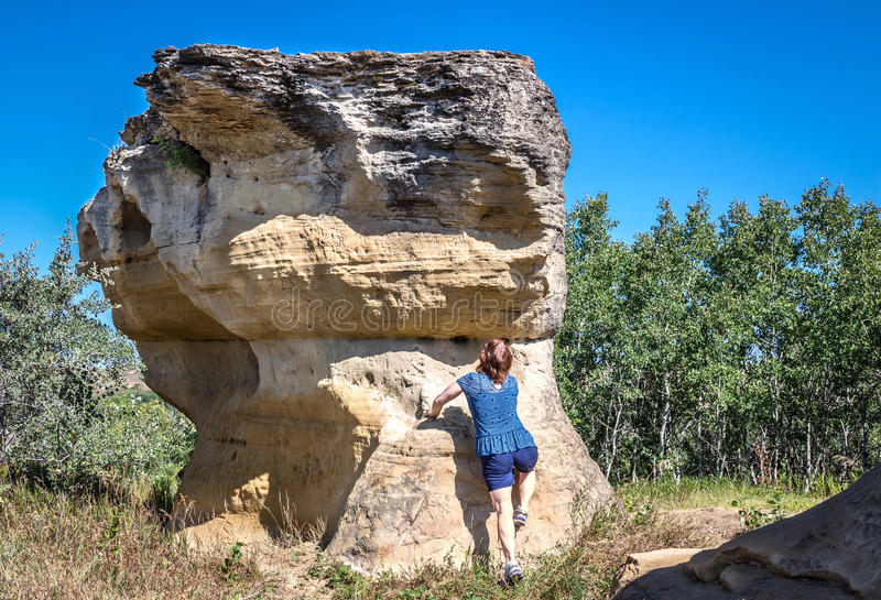 Woman trying to climb up a natural sandstone rock formation. Horizontal image of a woman trying to climb up the side of a sandstone rock formation in the summer royalty free stock photography