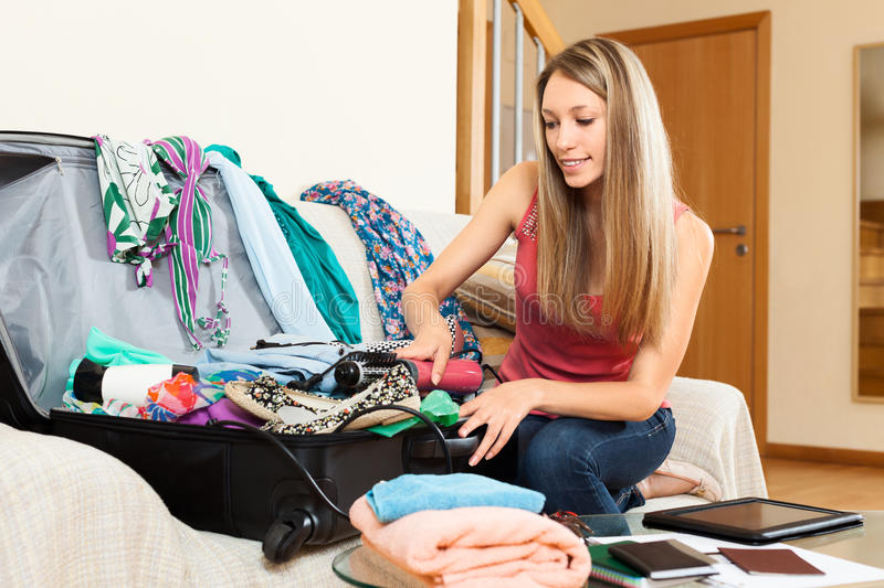 Woman trying to find room for all the things in trunk royalty free stock image