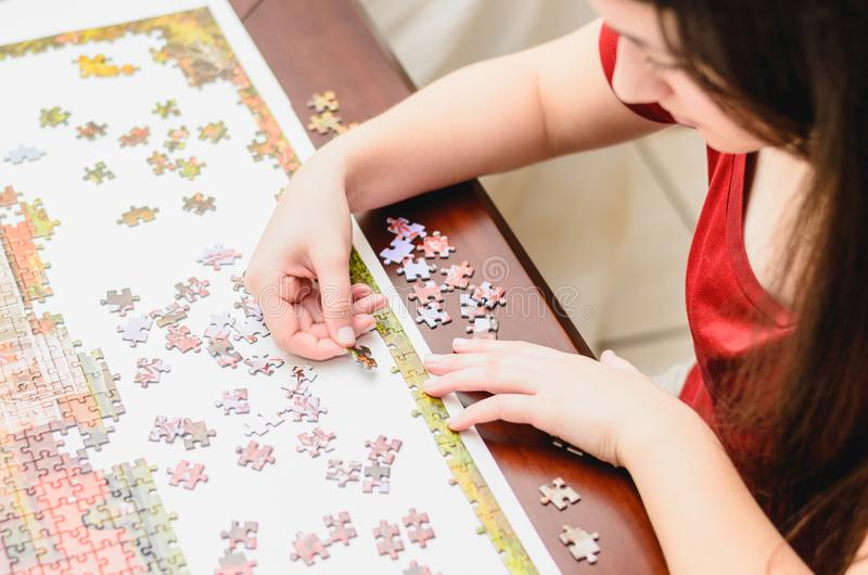 Woman trying to match pieces of a Jigsaw Puzzle Game. Playing the game, top view royalty free stock photo