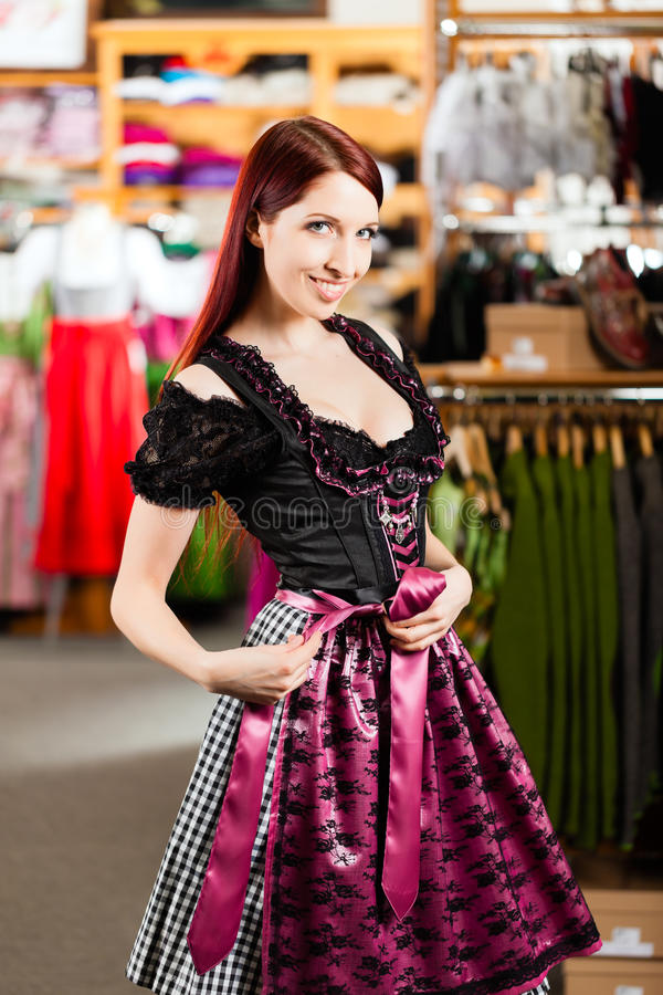 Woman is trying Tracht or dirndl in a shop stock photography