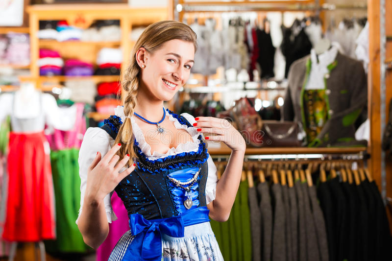 Woman is trying Tracht or dirndl in a shop royalty free stock photography