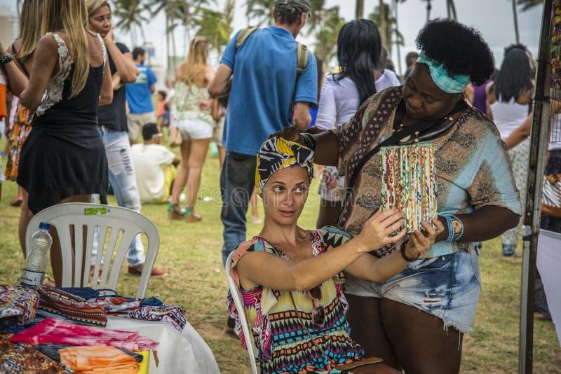Woman trying on a turban, Salvador, Bahia, Brazil. Woman trying on a turban at the crafts fair at the Festival da Primavera in Jardim de Alah, Salvador, Bahia royalty free stock images