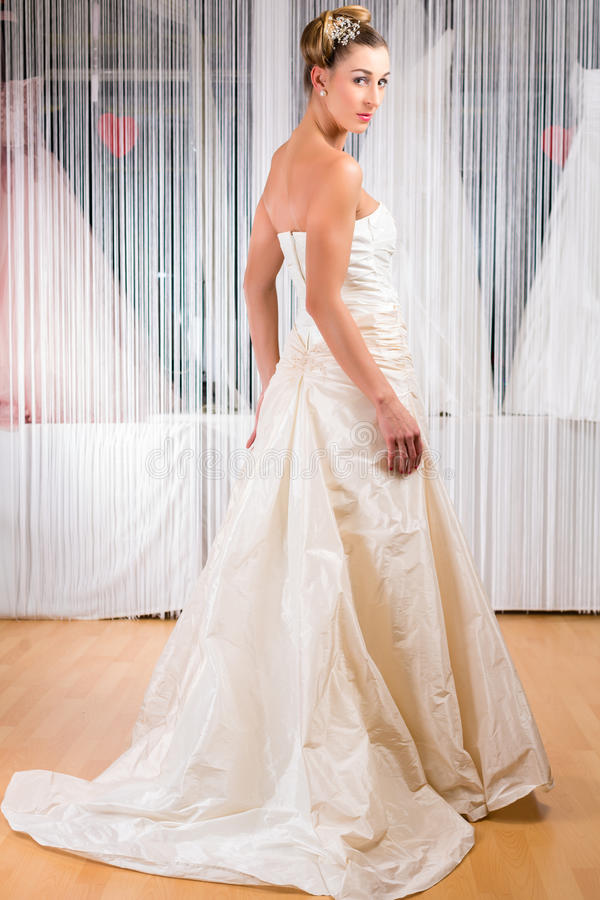 Woman trying wedding dress in shop royalty free stock photos