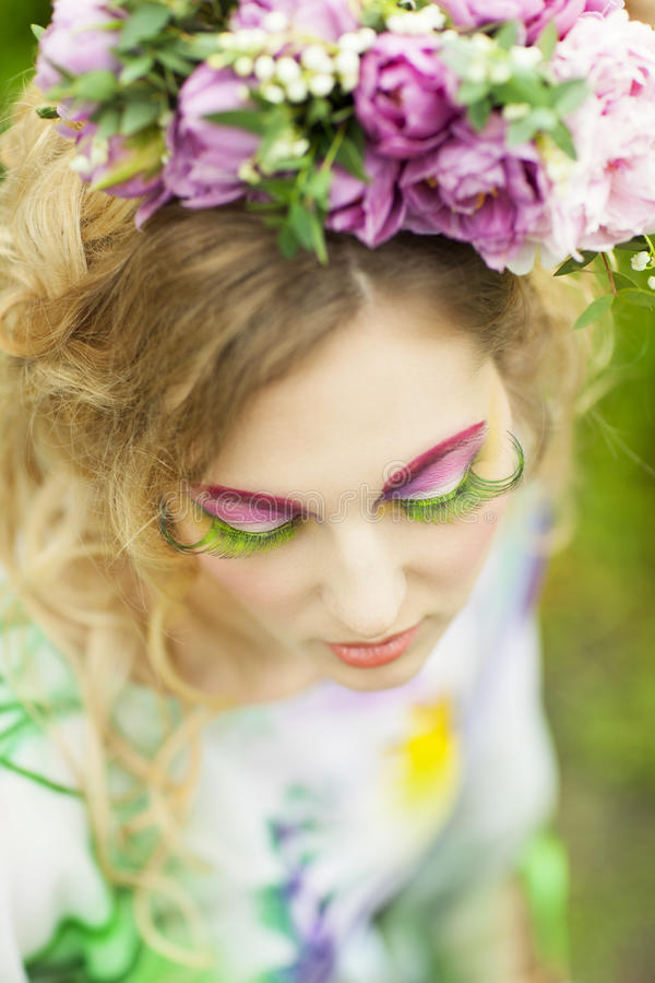 Woman with tulips, lily of the valley and pink peony in her hair. Portrait of a young woman with tulips, lily of the valley and pink peony in her hair stock photography