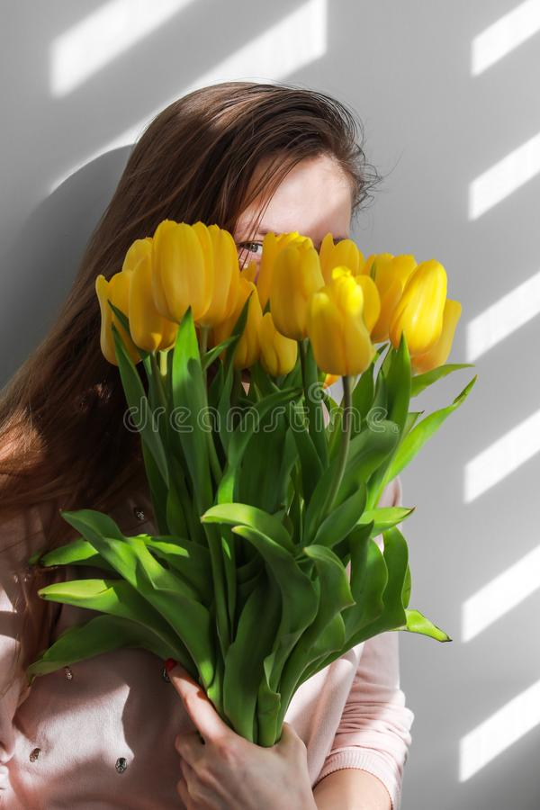 Woman with tulips. Young female with yellow flowers tulip natural portrait lifestyle near white background. Young female with yellow flowers tulip natural royalty free stock images