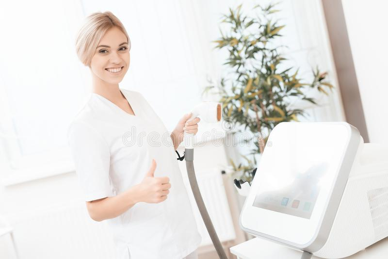 A woman tunes a laser hair removal machine. She holds a working part of the epilator in her hands and poses for a photo. It is located in a modern beauty salon royalty free stock images
