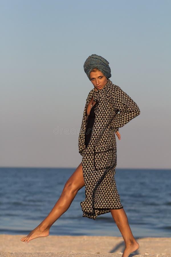 Woman in turban and coat posing on sandy sea beach royalty free stock photos