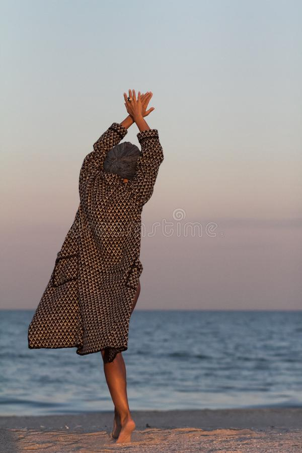 Woman in turban and coat on sandy sea beach back view royalty free stock photo
