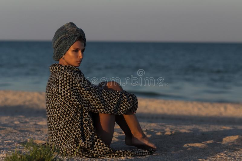 Woman in turban and coat sitting on sandy sea beach royalty free stock photo