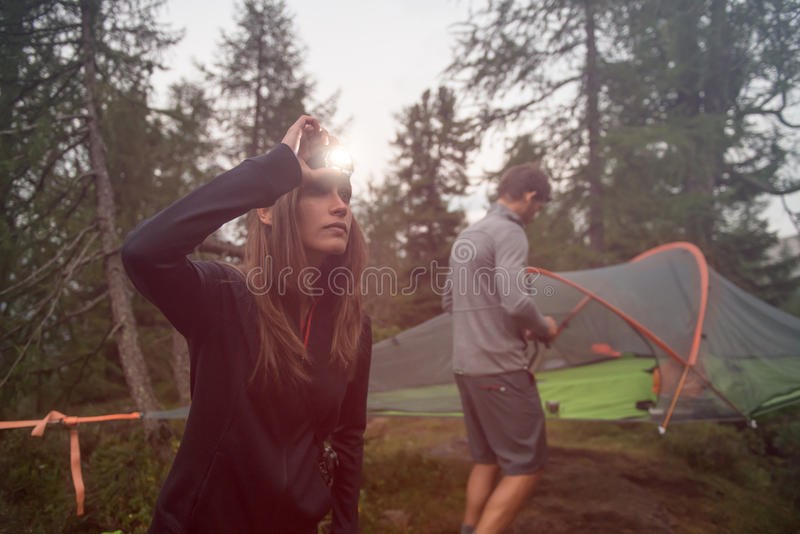 Woman turning on headlamp flashlight near hanging tent camping. Group of friends people summer adventure journey in. Mountain nature outdoors. Travel exploring royalty free stock photos