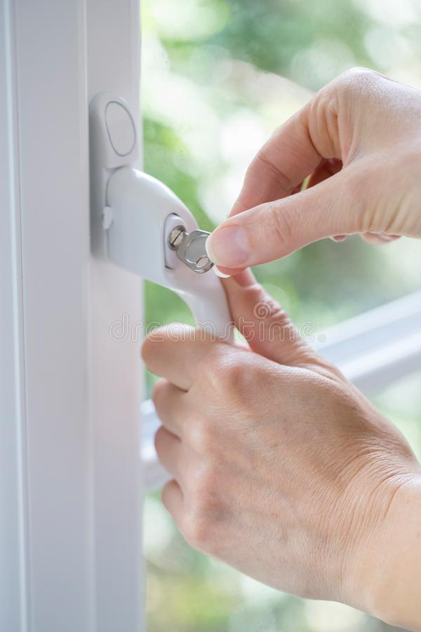 Close Up Of Woman Turning Key In Window Lock royalty free stock image