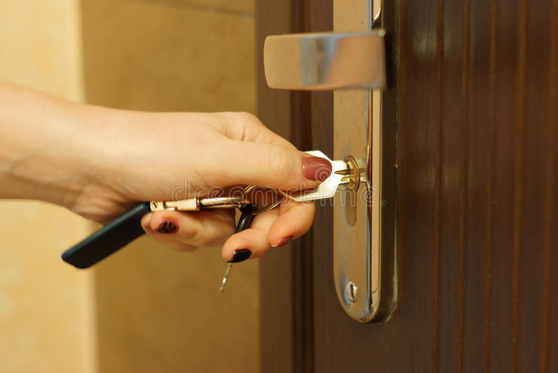 Woman turns the key in a lock on an external door royalty free stock photography