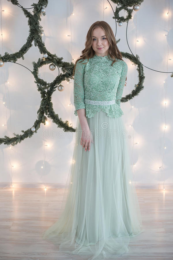Woman in turquoise evening dress of a white wall decorated stock photography