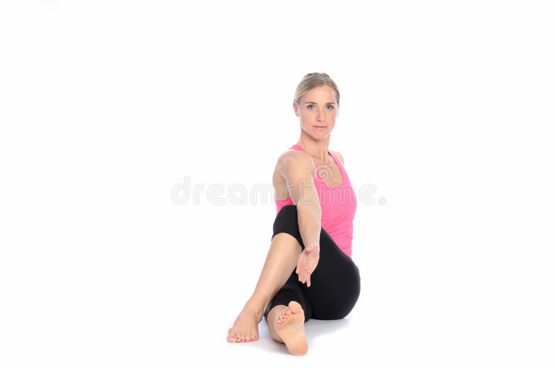 Woman twisting herself for a stretch. Beautiful athletic woman with calm expression twisting herself for a stretch over isolated white background royalty free stock images