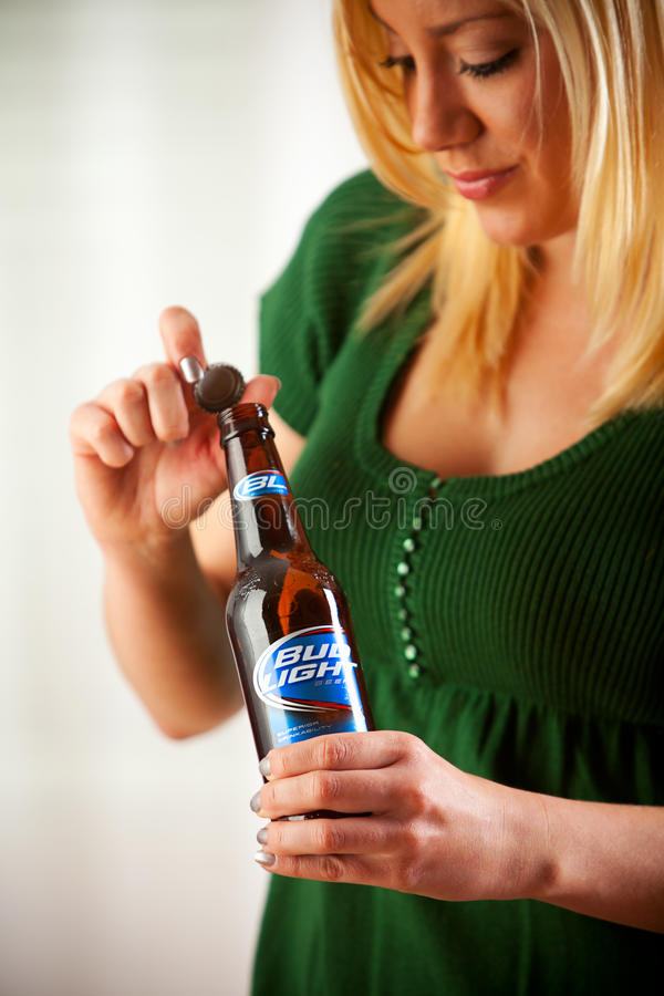 Woman Twists Cap Off Of Bottle Of Bud Light. Bud Light Is Produced By Anheuser-Busch. royalty free stock photos