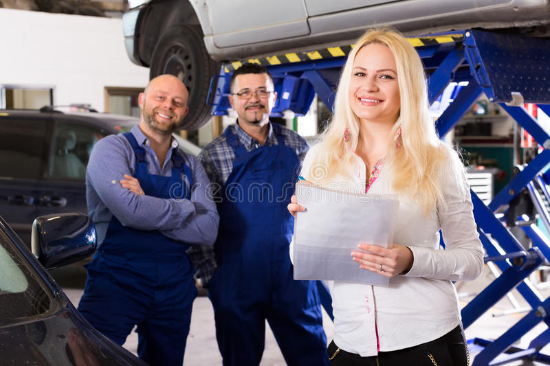 Woman and two auto mechanics. Attractive female insurance agent discussing with auto mechanics renewal of car. Focus on girl stock photos