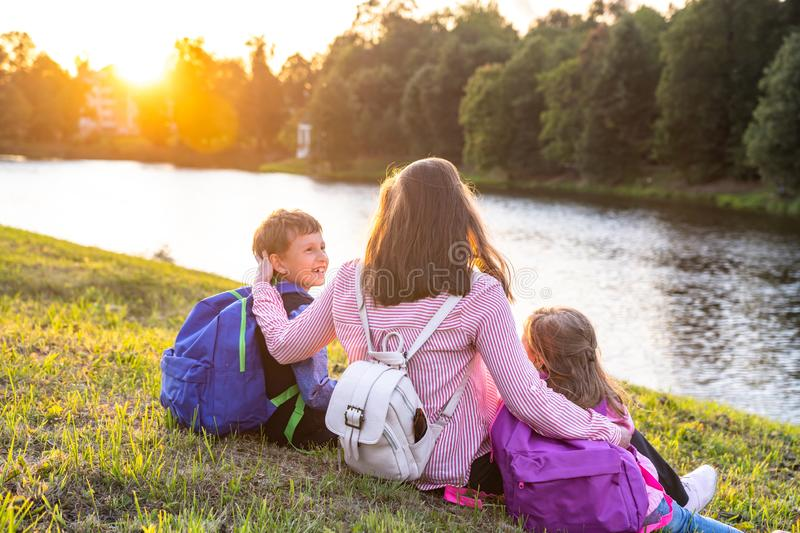 Woman and two children from back. Mother is resting sitting outdoors near the pond with kids by schoolchildren on way home. children with briefcases are from stock photo