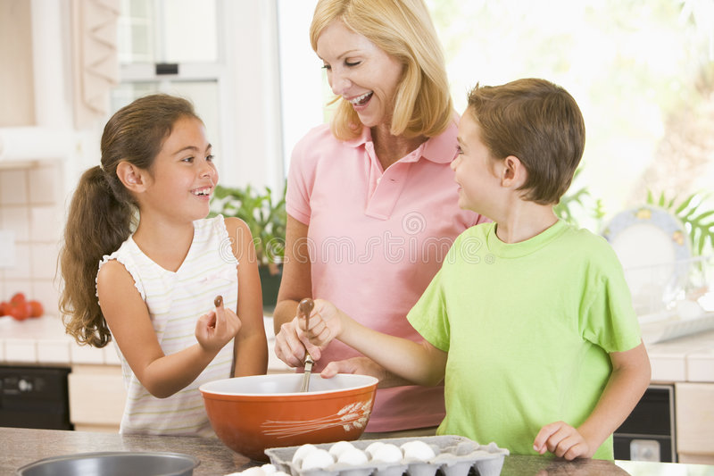 Woman and two children in kitchen baking royalty free stock photography