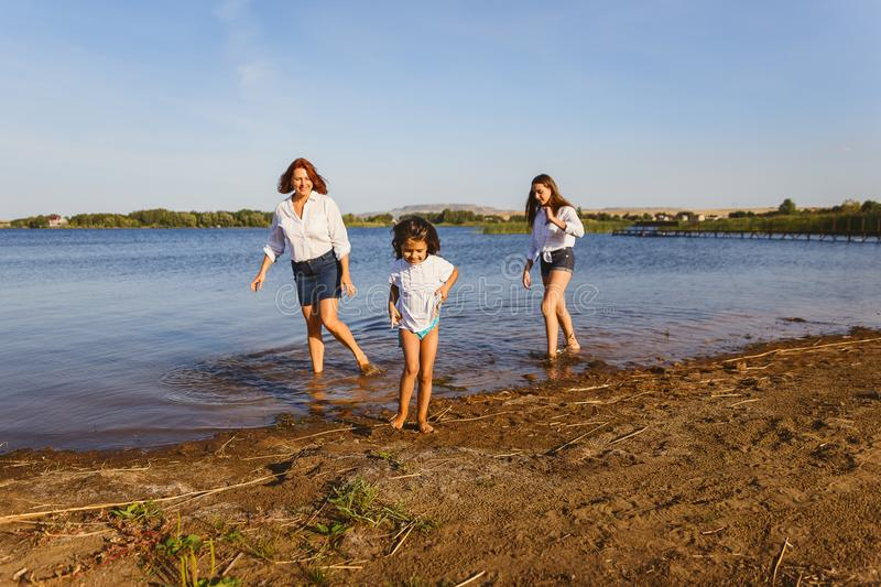 Woman with two daughters walking along the lake shore stock photo