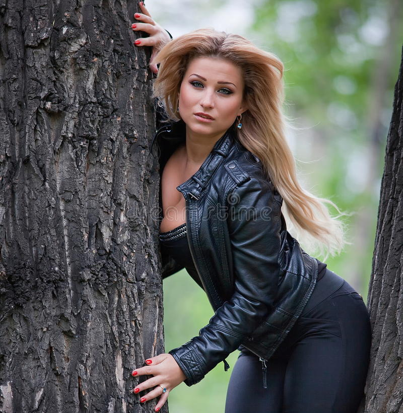 Woman between two trees. Beautiful, woman posing between two large trees royalty free stock images