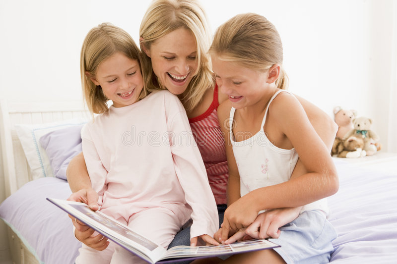 Woman and two young girls in bedroom reading book stock image